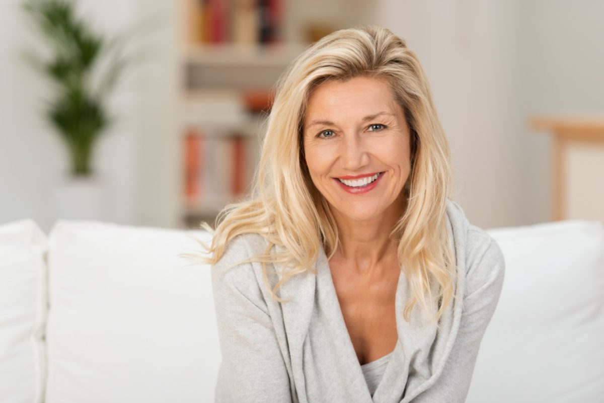 Blond woman with a beaming smile sitting on a sofa