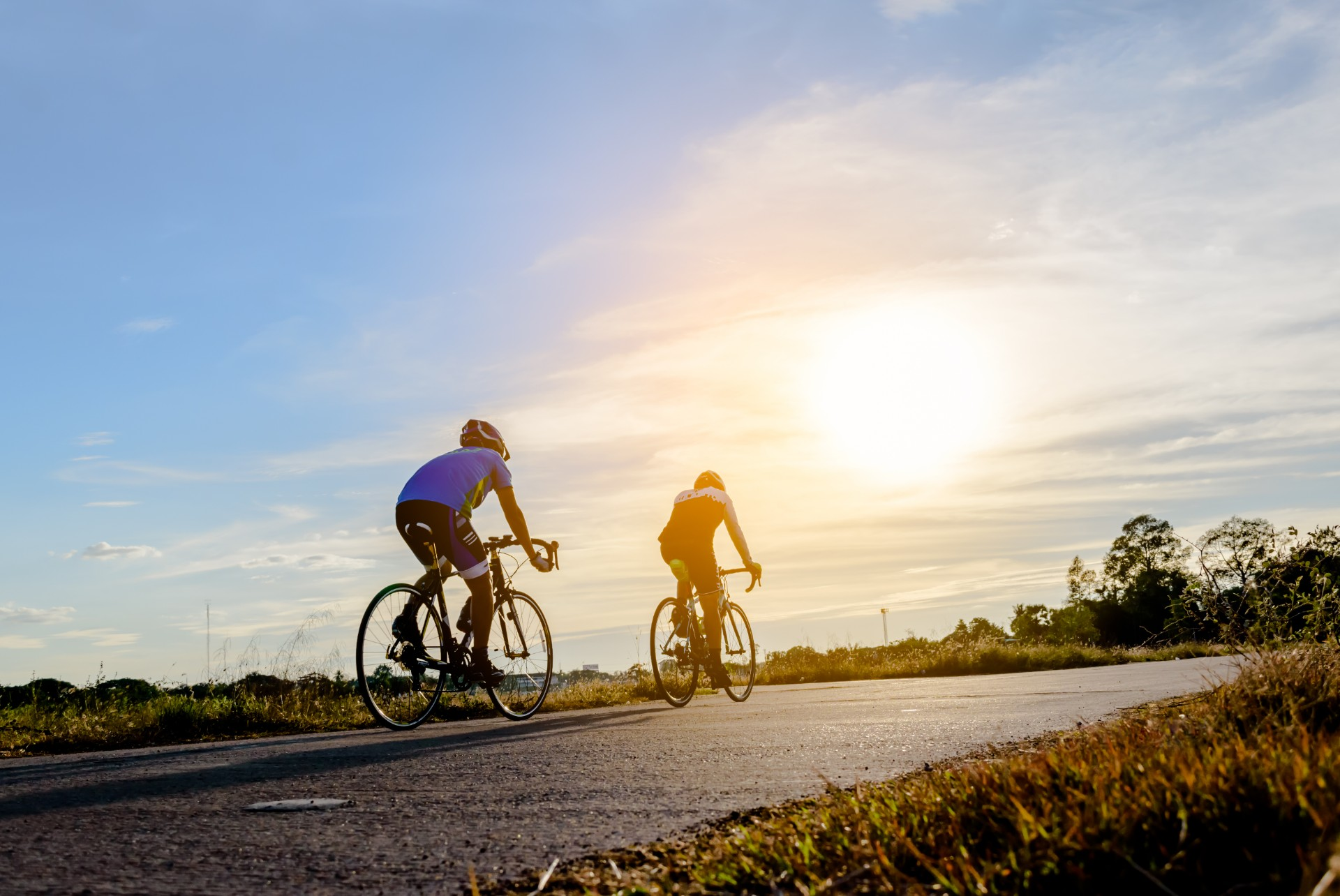 Two men ride on bike on the road